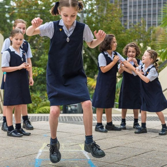 Girls playing hopscotch at school