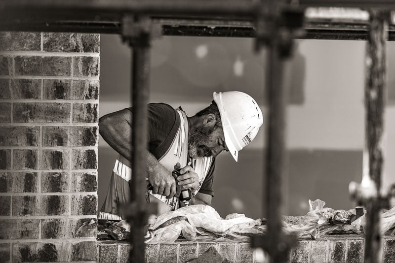 carpenter drilling on building site