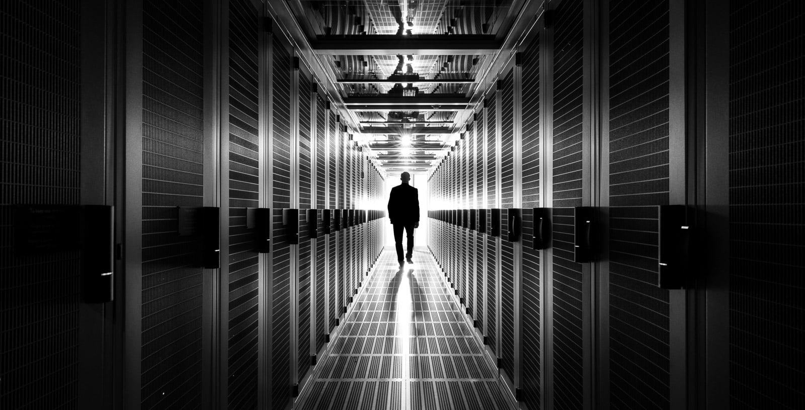 man walking in aisle of data centre