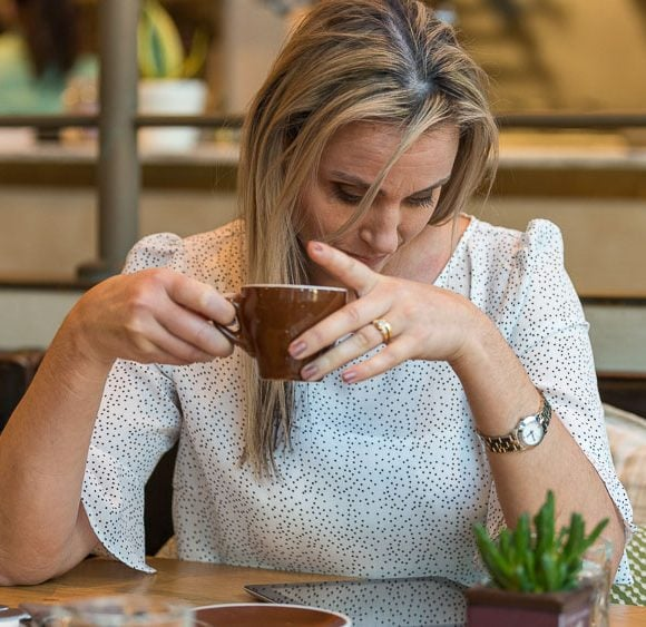 on-location photography - woman having coffee and checking her iPad