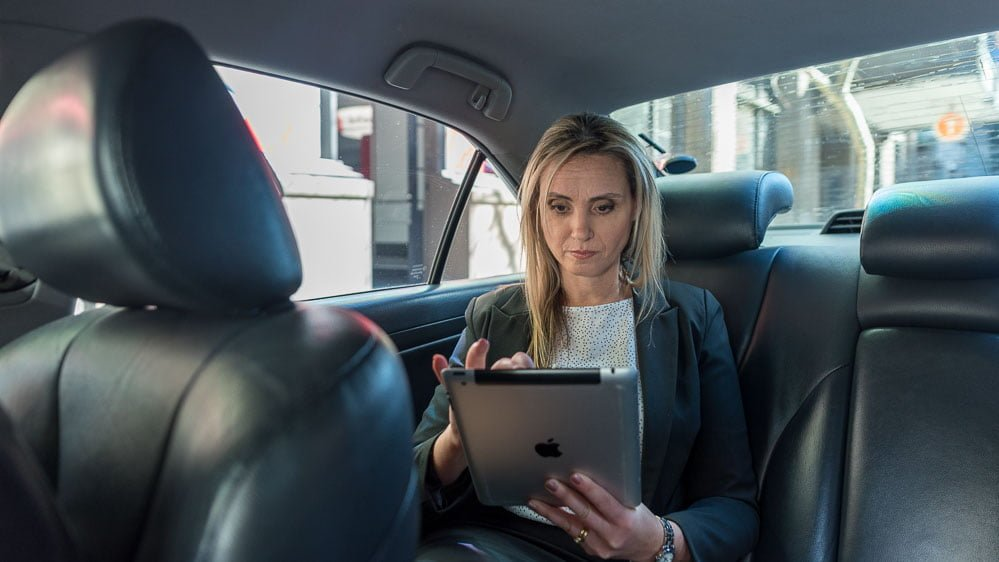 mobile on-location photography - woman in taxi checking iPad