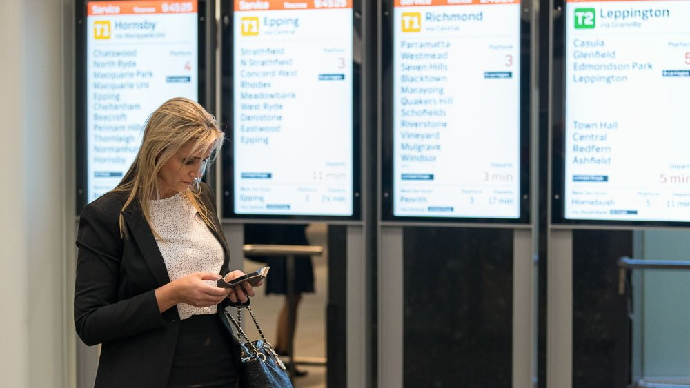 On an on-location portrait of a woman at train station checking her phone