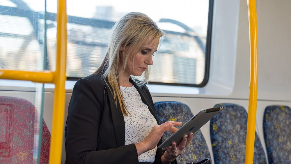 On an on-location portrait of a woman checking iPad on train