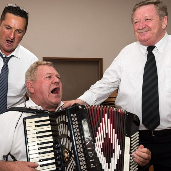 accordion player and two singers